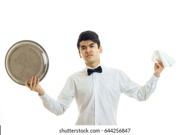 the young angry waiter in a white shirt holding a tray of crockery and napkin