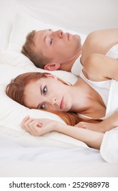Young angry woman lying in bed with her husband