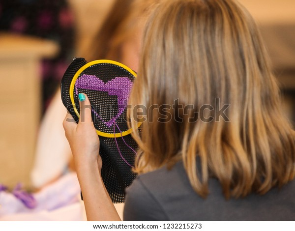 A young, anonymous girl is embroidering a purple heart by hand in a class at school. She is seen from behind, focus on the handiwork.