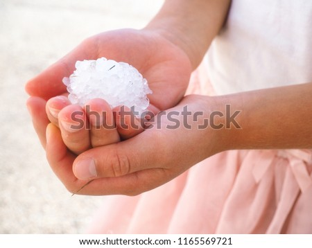 Young anonymous girl with hands filled with granule hail ice crystals, wearing pink dress and shirt