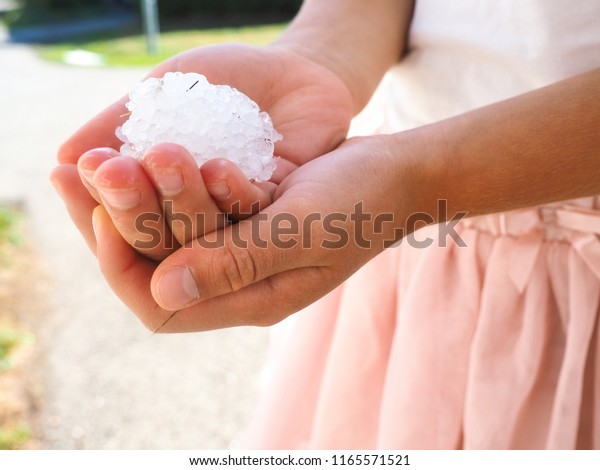 Young anonymous girl with hands filled with granulated hail ice crystals, wearing pink dress and shirt