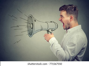 Young anxious man shouting with anger posing with painted loudspeaker.