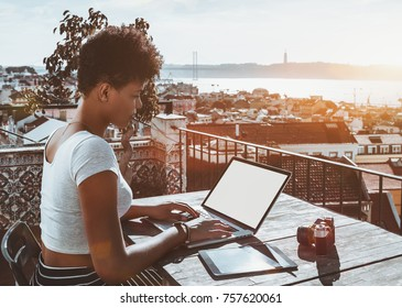 Young appealing biracial female photographer sitting on balcony of Lisbon hotel with stunning bright cityscape in background and working with laptop mock-up; retro photo camera and tablet pc near her
