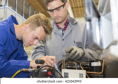 young apprentice with heating professional