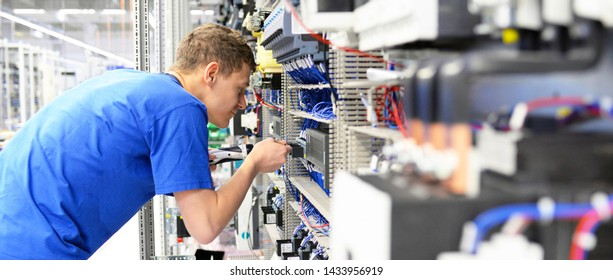 young apprentice worker in an industrial company assembling electronic components in the mechanical engineering of a modern factory