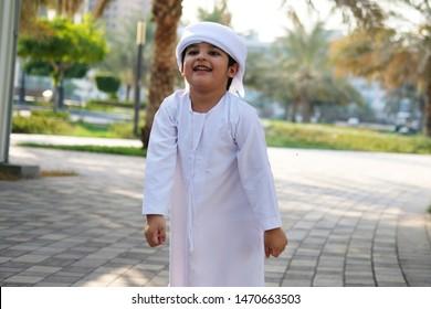Young Arab Boy walking while smiling wearing traditional Emirati Kandura