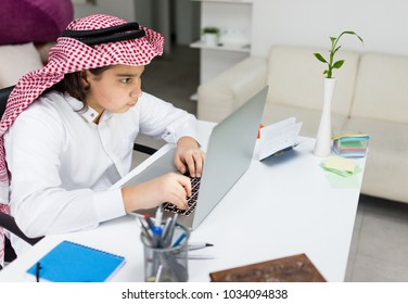 Young Arab Boy Working on Laptop on Desk