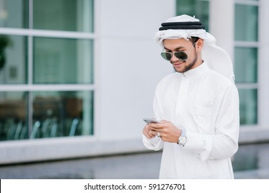 Young Arab businessman using mobile phone while walking in the city.