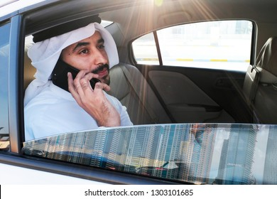 Young Arab emirati man wearing kandora thobe while holding his cellphone inside a car looking outside the window