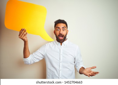 Young arab indian hispanic man holding speech bubble over isolated white background very happy and excited, winner expression celebrating victory screaming with big smile and raised hands