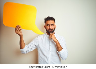 Young arab indian hispanic man holding speech bubble over isolated white background serious face thinking about question, very confused idea