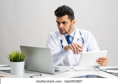 Young arab internist working with tablet computer. Physician in white medical gown with stethoscope sitting at desk with laptop. Professional medical consultation and treatment in modern clinic.