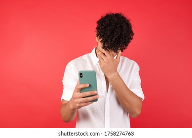 A Young arab man with afro hair wearing shirt standing over isolated red background looking at smart phone feeling sad holding hand on face.