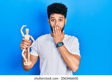 Young arab man with beard holding small wooden manikin covering mouth with hand, shocked and afraid for mistake. surprised expression