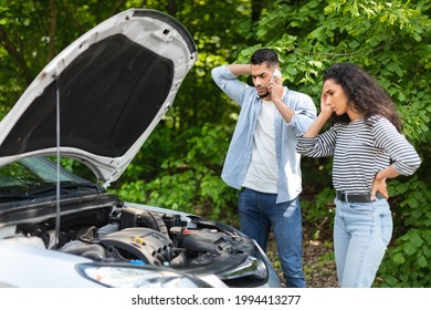 Young arab man calling for help on mobile phone. Upset middle-eastern couple having broken car while countryside trip, calling auto service, looking at engine and touching their heads