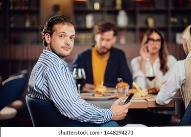 Young arab man dressed smart casual sitting at dinner in restaurant and using smart phone.