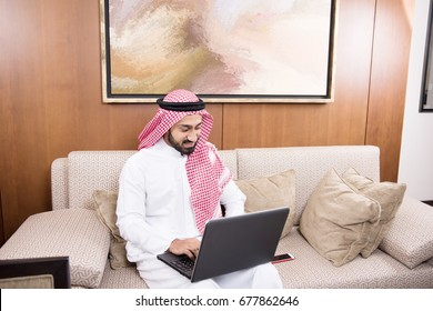 Young Arab man in traditional dress using laptop