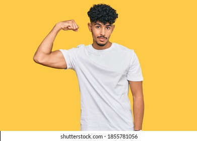 Young arab man wearing casual white t shirt strong person showing arm muscle, confident and proud of power