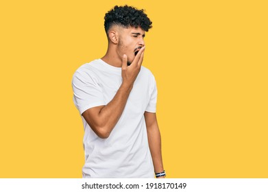 Young arab man wearing casual white t shirt bored yawning tired covering mouth with hand. restless and sleepiness.
