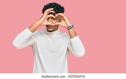 Young arab man wearing casual winter sweater doing heart shape with hand and fingers smiling looking through sign
