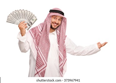 Young Arab spreading a stack of money and making a welcoming gesture with his hand isolated on white background