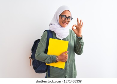 Young Arab student woman wearing hijab and backpack holding a book over isolated background doing ok sign with fingers, excellent symbol