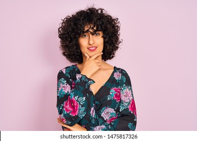 Young arab woman with curly hair wearing floral dress over isolated pink background looking confident at the camera with smile with crossed arms and hand raised on chin. Thinking positive.