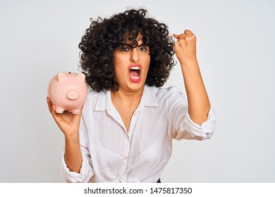 Young arab woman with curly hair holding piggy bank over isolated white background annoyed and frustrated shouting with anger, crazy and yelling with raised hand, anger concept