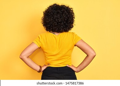 Young arab woman with curly hair wearing t-shirt standing over isolated yellow background standing backwards looking away with arms on body