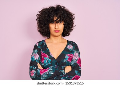Young arab woman with curly hair wearing floral dress over isolated pink background skeptic and nervous, disapproving expression on face with crossed arms. Negative person.