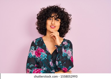 Young arab woman with curly hair wearing floral dress over isolated pink background looking confident at the camera smiling with crossed arms and hand raised on chin. Thinking positive.