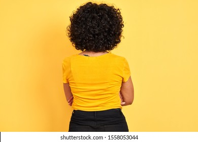 Young arab woman with curly hair wearing t-shirt standing over isolated yellow background standing backwards looking away with crossed arms