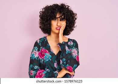 Young arab woman with curly hair wearing floral dress over isolated pink background thinking looking tired and bored with depression problems with crossed arms.