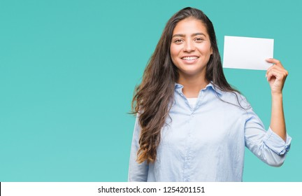 Young arab woman holding blank card over isolated background with a happy face standing and smiling with a confident smile showing teeth