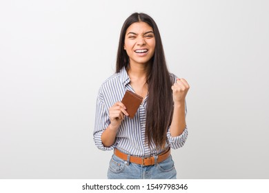 Young arab woman holding a wallet cheering carefree and excited. Victory concept.
