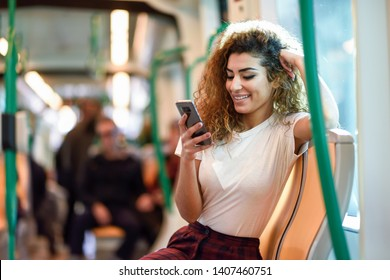 Young Arab woman inside subway train looking at her smart phone. Female in casual clothes.