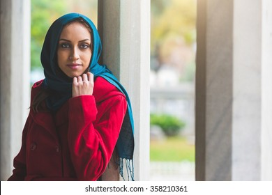 Young arab woman portrait in Istanbul. She is a caucasian woman on her mid twenties, wearing a veil and a red coat, leaning to a column and looking at camera. Travel and religions concepts.