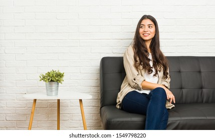 Young arab woman sitting on the sofa looks aside smiling, cheerful and pleasant.