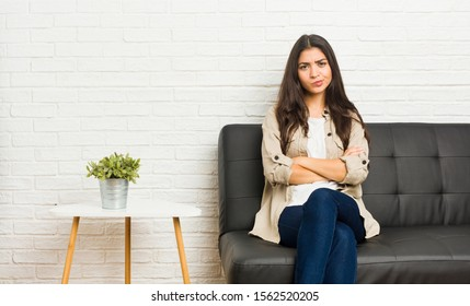 Young arab woman sitting on the sofa frowning face in displeasure, keeps arms folded.
