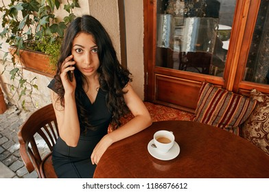 young Arab woman talking on the phone at the cafe