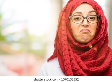 Young arab woman wearing hijab having skeptical and dissatisfied look expressing Distrust, skepticism and doubt