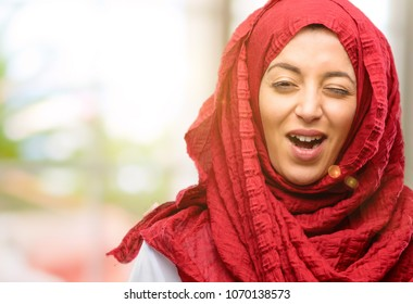 Young arab woman wearing hijab blinking eyes with happy gesture