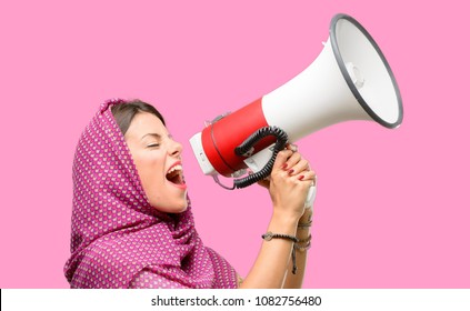 Young arab woman wearing hijab communicates shouting loud holding a megaphone, expressing success and positive concept, idea for marketing or sales