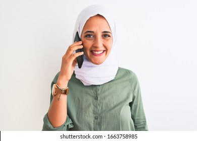 Young Arab woman wearing hijab talking on smartphone over isolated background with a happy face standing and smiling with a confident smile showing teeth