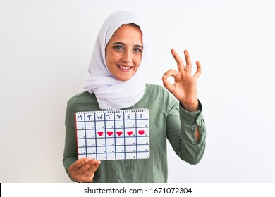 Young Arab woman wearing hijab showing menstruation calendar over isolated background doing ok sign with fingers, excellent symbol