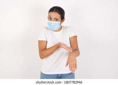 Young arab woman wearing medical mask standing over isolated white background In hurry pointing to watch time, impatience, upset and angry for deadline delay.