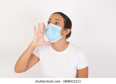 Young arab woman wearing medical mask standing over isolated white background shouting and screaming loud to side with hand on mouth. Communication concept.