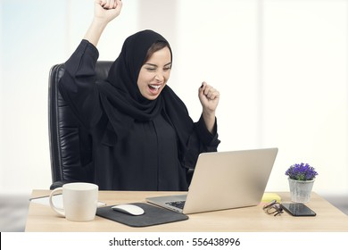Young Arabian businesswoman expressing success at office