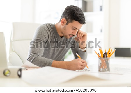 Young Arabian Male Contractor Analyzing Blueprint Stock Photo (Edit