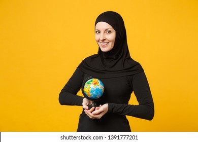 Young arabian muslim student girl in hijab black clothes hold in hands Earth world globe isolated on yellow wall background, studio portrait. People religious lifestyle concept. Mock up copy space